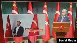 Recep Tayyip Erdoğanın çıxışı zamanı ekranda Orhan İnandı əlləri qandallı vəziyyətdə nümayiş etdirilirdi