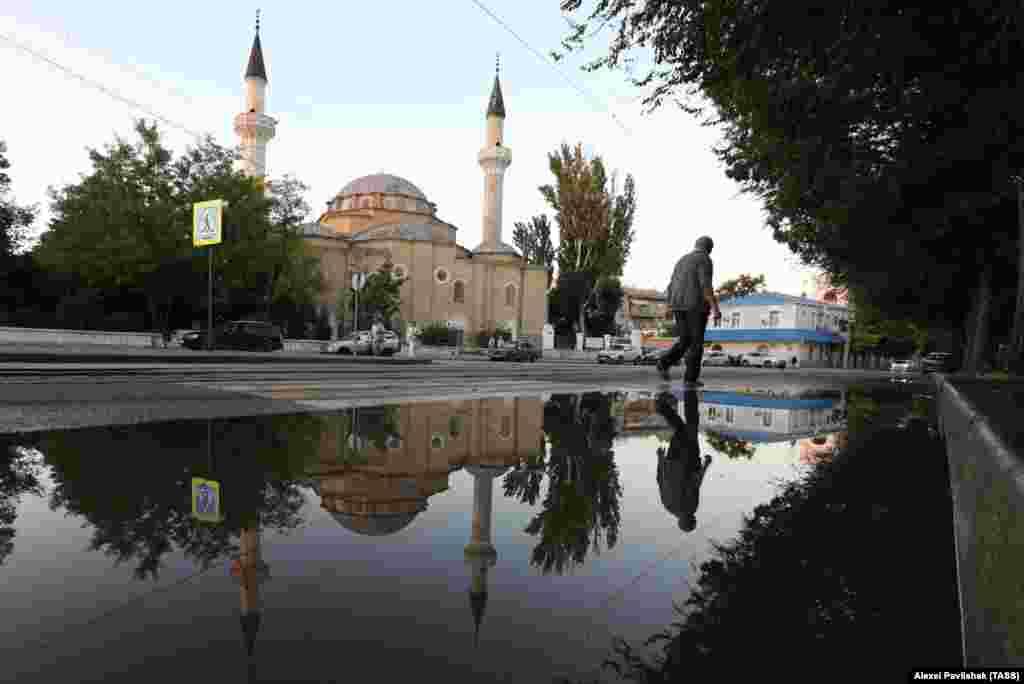 Мечеть Джума-Джами отражается в луже после недавнего дождя