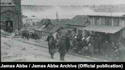 Рабочие стоят в очереди в пункт выдачи пищи, который еще не начал работу. На заднем плане – дамба Днепрогэса. Эббе писал, что в СССР любую очередь снимать запрещено. Особенно если это очередь за едой. Фото 1932 года. James Abbe/James Abbe Archive