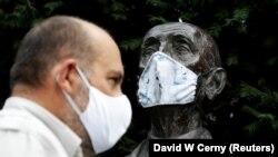 A prágai állatkert igazgatója maszkban az intézmény alapítójának szobra mellett.