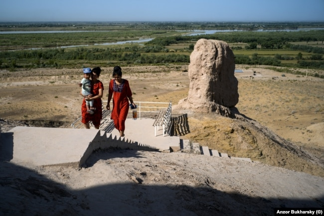 Two Uzbek women climb to the top of the tower of silence.