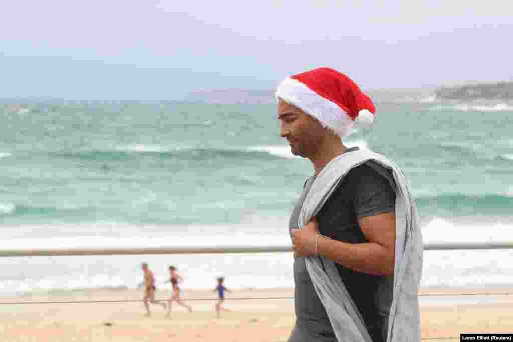 Mikulássapkában és törölközővel a vállán sétál az ausztrál tengerparton ez a férfi december 25-én Sydneyben.