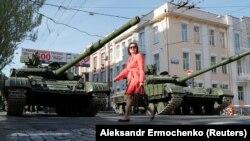 Донеччанка переходить вулицю Артема в Донецьку перед танками бойовиків на репетиції параду до 9 травня