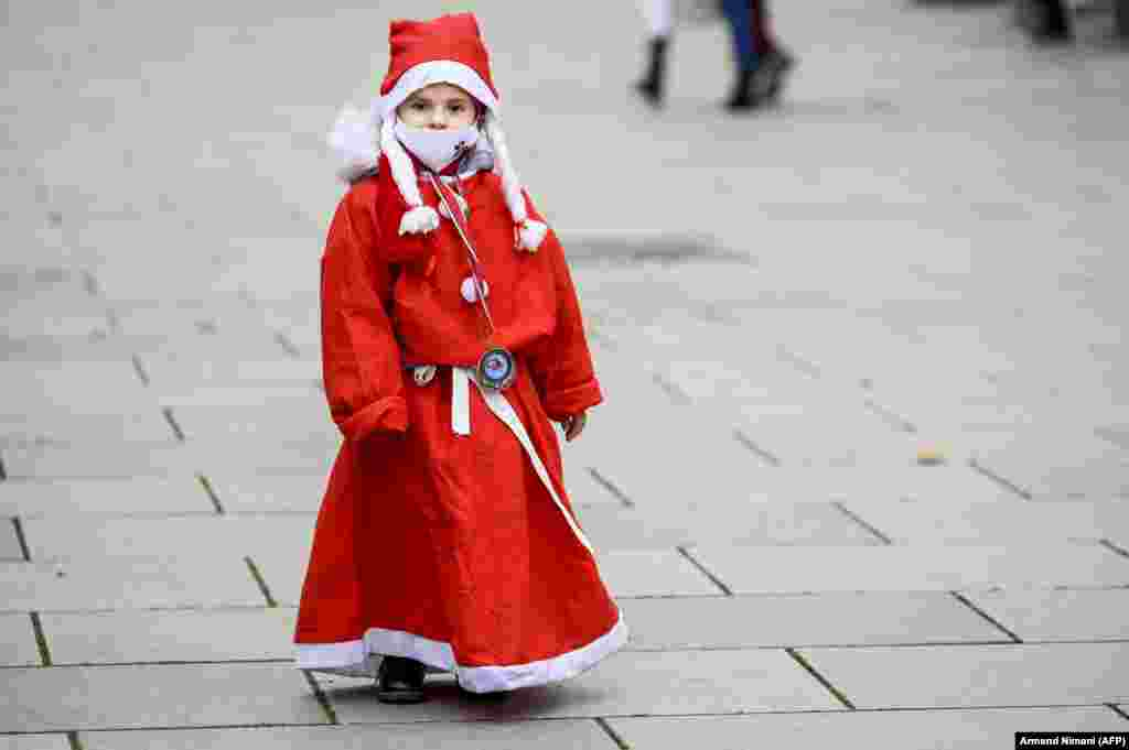 A child dressed as Santa Claus takes part in a charity event in Pristina to raise funds for families in need in Kosovo, amid the COVID-19 pandemic. (AFP/Armend Nimani)