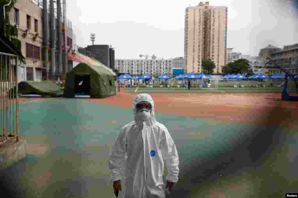 Співробітник служби охорони в захисному костюмі підходить до фотографа на полігоні спортивного центру Гуанган після несподіваного спалаху коронавірусної хвороби (COVID-19) у Пекіні, Китай