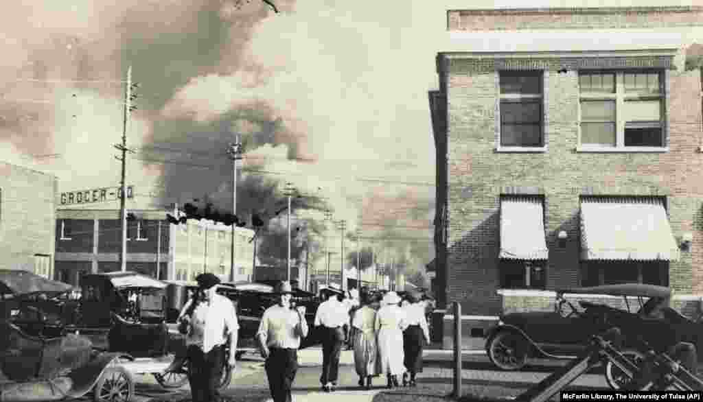 Two armed men walk away from burning buildings as others walk in the opposite direction during the June 1, 1921, Tulsa.
