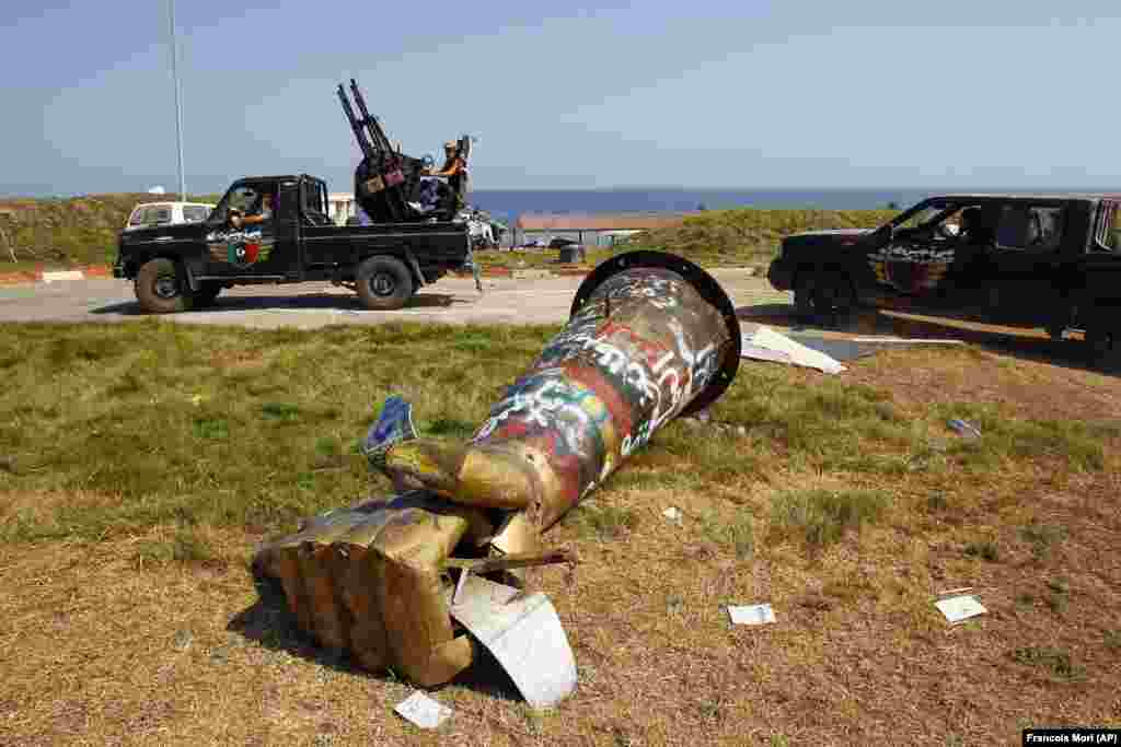 Покрит с графити монумент на юмрук, смазващ американски военен самолет, издигнат някога в Триполи, Либия. Известната скулптура е свалена по време на гражданската война през 2011 г. и се смята, че сега е в Музея на Либия.