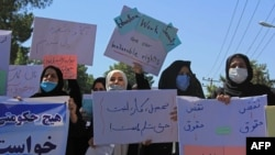 Afghan women hold placards as they take part in a protest in Herat on September 2.