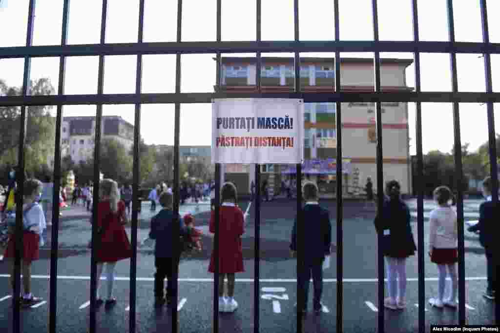 Ученици и учители спазват социална дистанция в училищен двор в Брашов, Румъния.
