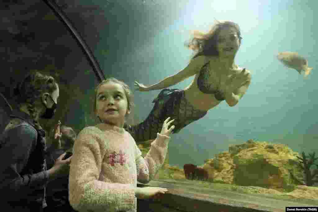 Disa vizitorë të rinj shikojnë një zhytëse të veshur si sirenë, në një akuarium në Yekaterinburg të Rusisë.