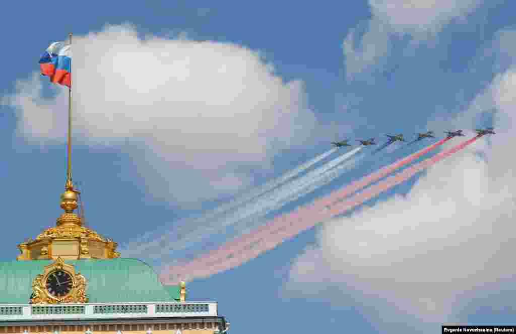 Російські літаки Су-25 випускають дим білого, синього і червоного кольорів російського прапора. Принаймні 75 військових літаків узяли участь у святкуванні Дня Перемоги