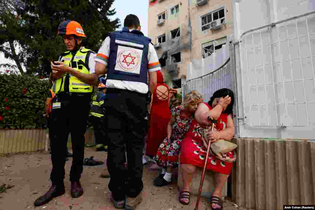 Israeli medics stand near women as they react after a residential building was damaged by a rocket launched from the Gaza Strip, in Ashkelon, southern Israel May 11, 2021.