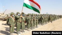 Members of Tajikistan's armed forces line up during joint military drills involving Russia, Uzbekistan, and Tajikistan at the Harb-Maidon training ground near the border with Afghanistan on August 10.