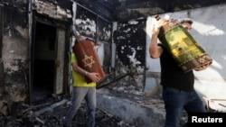 Мъже изнасят свитъци на Тората от опожарена синагога в град Лод, Израел. 12 май 2021 г.