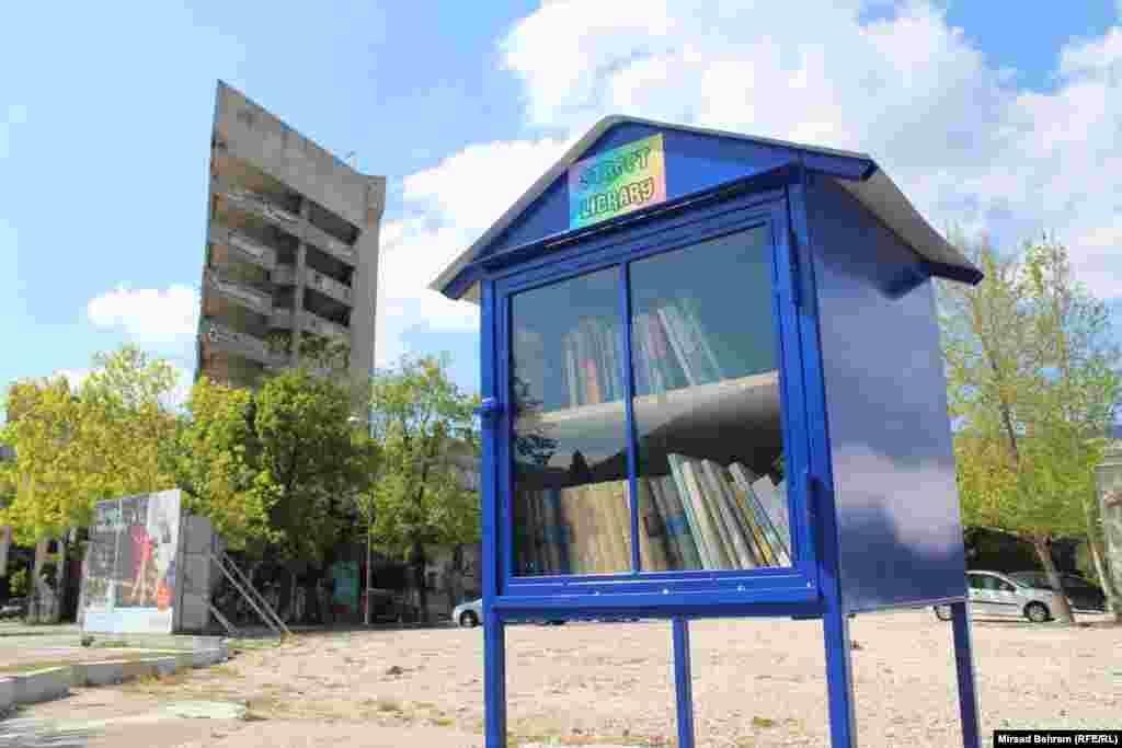 """Jedna od uličnih biblioteka u Mostaru postavljena je i u centru grada, na bivšoj, ratnoj liniji razdvajanja. U pozadini se vidi porušena zgrada, među Mostarcima do 1992. godine poznata i kao """"Staklena banka"""""""