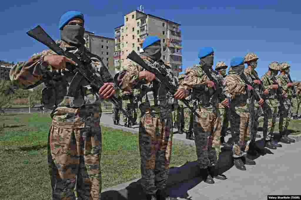 """Azerbaijani servicemen during a parade in Susa/Shushi on September 27. In a speech, Azerbaijan's authoritarian president referred to the 2020 fighting, in which vast tracts of Azerbaijani land was retaken from ethnic Armenian fighters, as a """"holy war"""" and declared, """"From now on, we will live as a victorious country, a victorious people, and we will build and restore the liberated lands."""""""