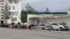 Люди сидят неподалеку от магазина в ожидании начала продажи продуктов питания. Государственный магазин №4 в 11-м микрорайоне Ашхабада. Май, 2021