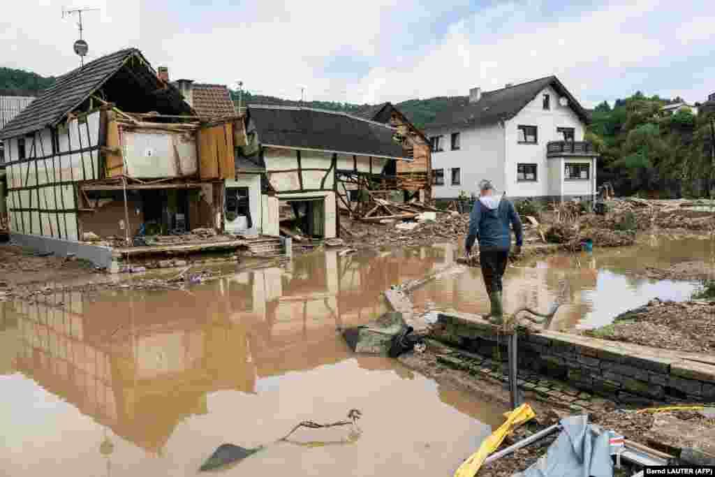 Мужчина идет к разрушенным домам в Шульде недалеко от Бад-Нойенара, Западная Германия, 15 июля 2021 года