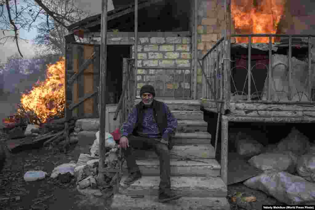 Part of a series titled Paradise Lost. Areg sits outside a burning house in the village of Karegakh, Nagorno-Karabakh, on 25 November 2020. Some village residents burned their houses before leaving areas that were to return to Azerbaijani control following the November peace agreement.  General News: First Prize, Stories - Valery Melnikov, Sputnik
