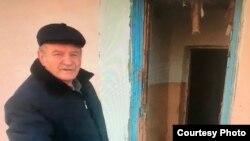 Көшіріліп жатқан Крестовский ауылының тұрғыны Николай Случик есігі бұзылған үйінің алдында тұр.