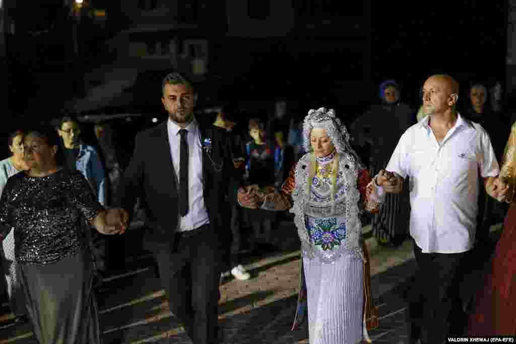 Сельма Демирович и ее жених Феджад Карадоллами (второй слева) танцуют с гостями во время свадьбы