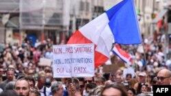 """Снимка от протестите в Париж на 31 юли. На плаката пише """"Не на здравния пропуск. Не на дискриминацията. Да на мира."""""""
