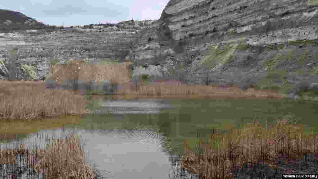 «Зворотний бік» Загайтанської скелі – кар'єр, величезний котлован з вертикальними випиляними стінами висотою до 50 метрів. На дні кар'єру утворилося невелике озеро з водою жовтуватого кольору
