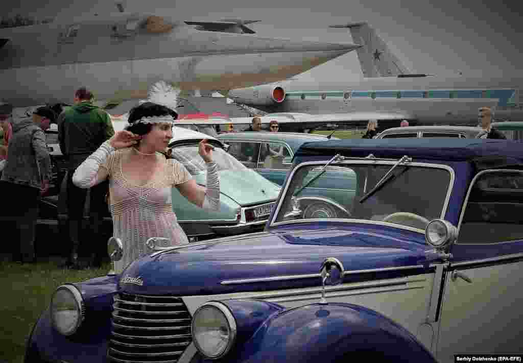 Женщина, одетая в ретро-костюм, позирует возле старой машины во время автосалона в Киеве, Украина