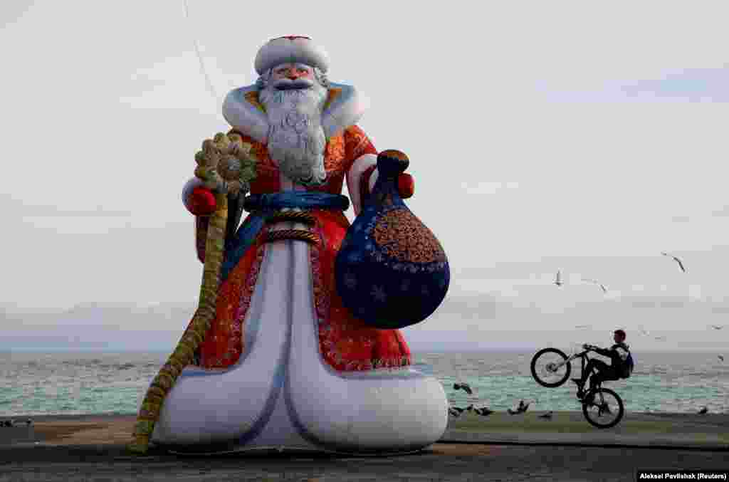 A bicyclist performs a trick on an embankment near an inflatable figure depicting Ded Moroz, the Russian equivalent of Santa Claus, ahead of the New Year and Christmas holiday season in the Black Sea resort of Alushta, Crimea. (Reuters/Alexey Pavlishak)