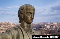 Tampilan dekat dari monumen perunggu, yang menampilkan belahan bumi yang dilapisi daun emas