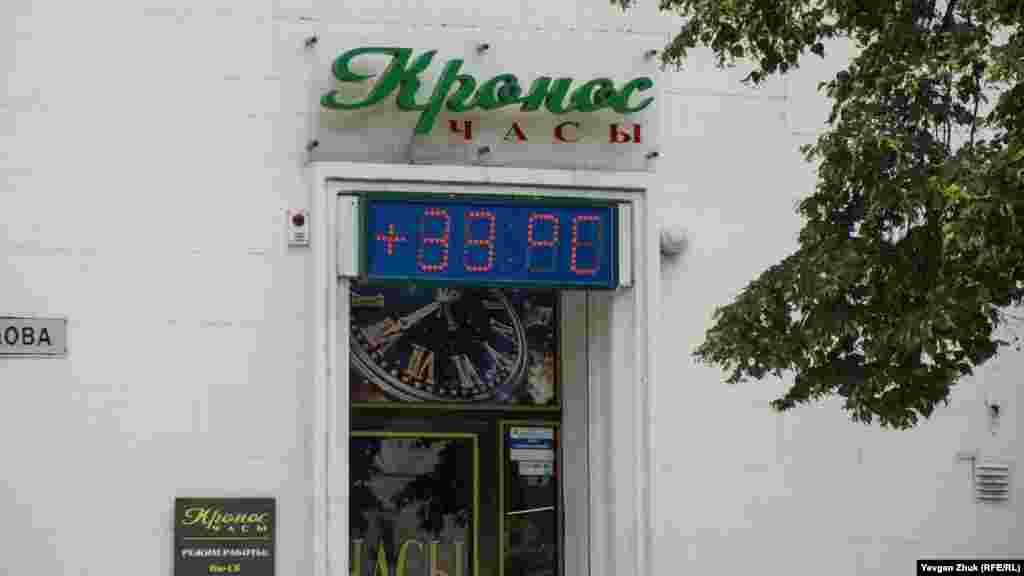 Табло магазина показывает температуру воздуха +33° поЦельсию