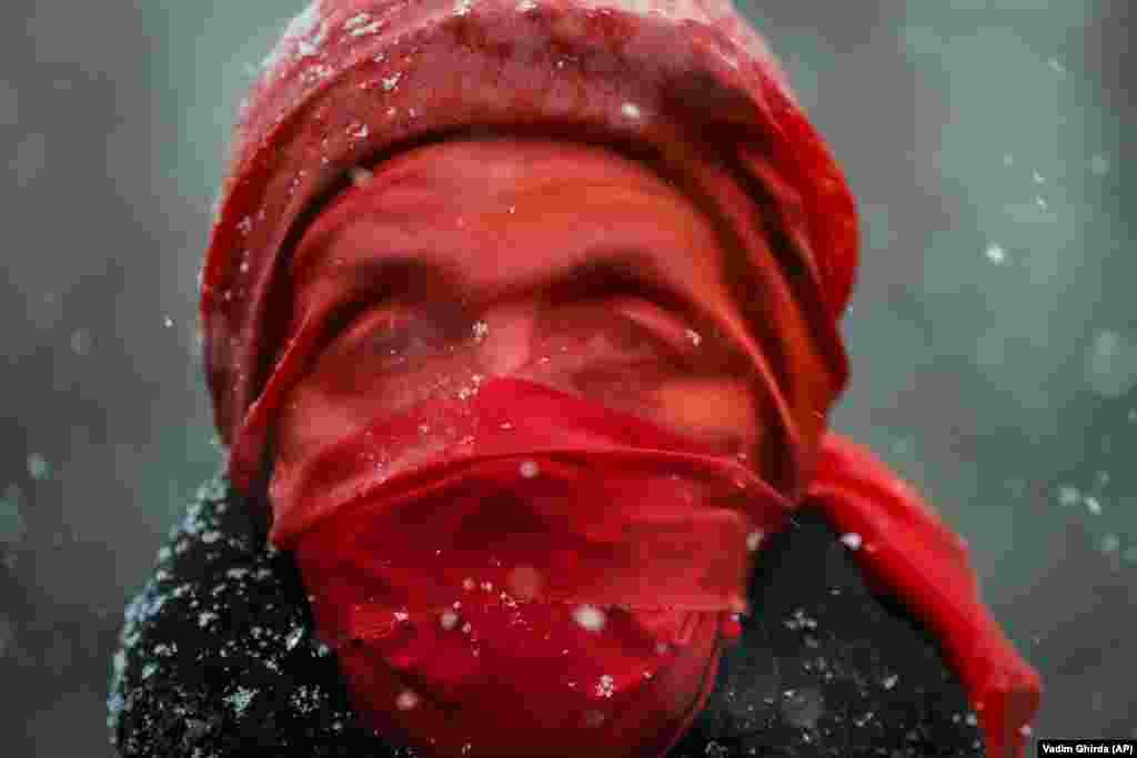 Një grua në Bukuresht ka vendosur këtë vello të kuqe gjatë një marshi sensibilizues kundër dhunës në familje. (AP/Vadim Ghirda)