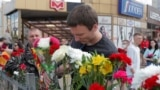 BELARUS -- A man places flowers near the site where a protester died on August 10 during a rally following the presidential election in Minsk, August 11, 2020