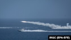 Iranian military fires a missile targeting a mock-up of U.S. aircraft carrier in the strategic Strait of Hormuz, July 28, 2020