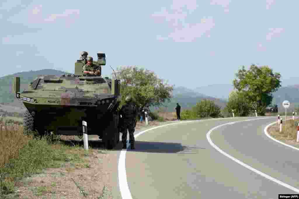 Солдаты сербской армии охраняют свою бронетехнику в селе Рудница, неподалеку от города Рашка на юге Сербии, 27 сентября. 26 сентября министр обороны СербииНебойша Стефанович посетил войска на двух военных базах неподалеку от границы с Косово в сопровождении посла России в Сербии
