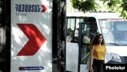 Armenia - A woman walks past a campaign billboard of the opposition Hayastan alliance in Yerevan, May 25, 2021.