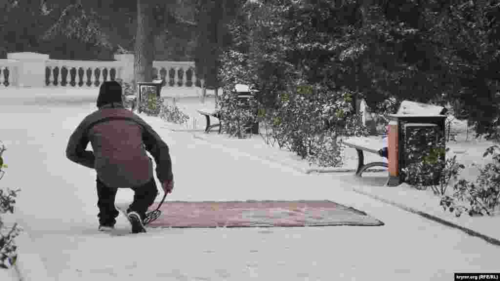Чоловік чистить килим на снігу