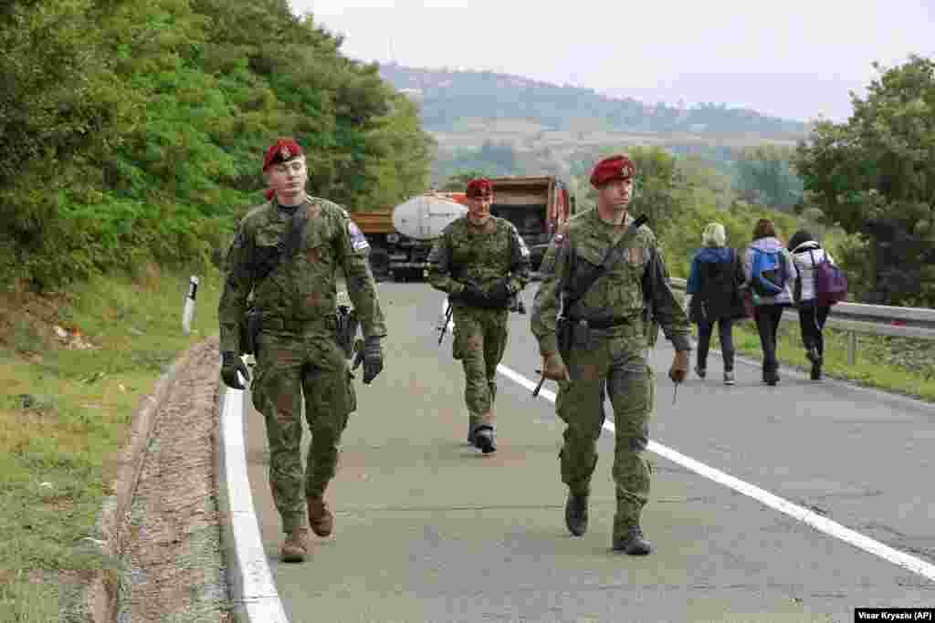 Польские солдаты изKFOR проходят через баррикады во время патрулирования неподалеку от КПП«Ярина», 28 сентября. KFOR поддерживается ООН, ЕС и другими международными организациями. Его цель–предотвратить сохранение межэтнической напряженности между этническими албанцами и сербами