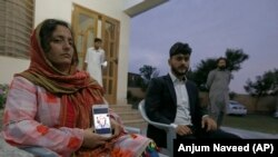 Kaneez Sughra, wife of prominent Pakistani journalist Matiullah Jan, shows a picture her husband to journalists.