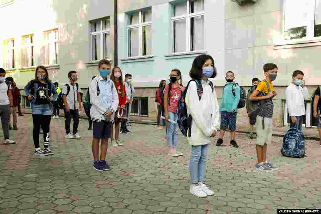Elementary-school students wearing face masks keep their distance on the first day of school in Pristina, Kosovo.