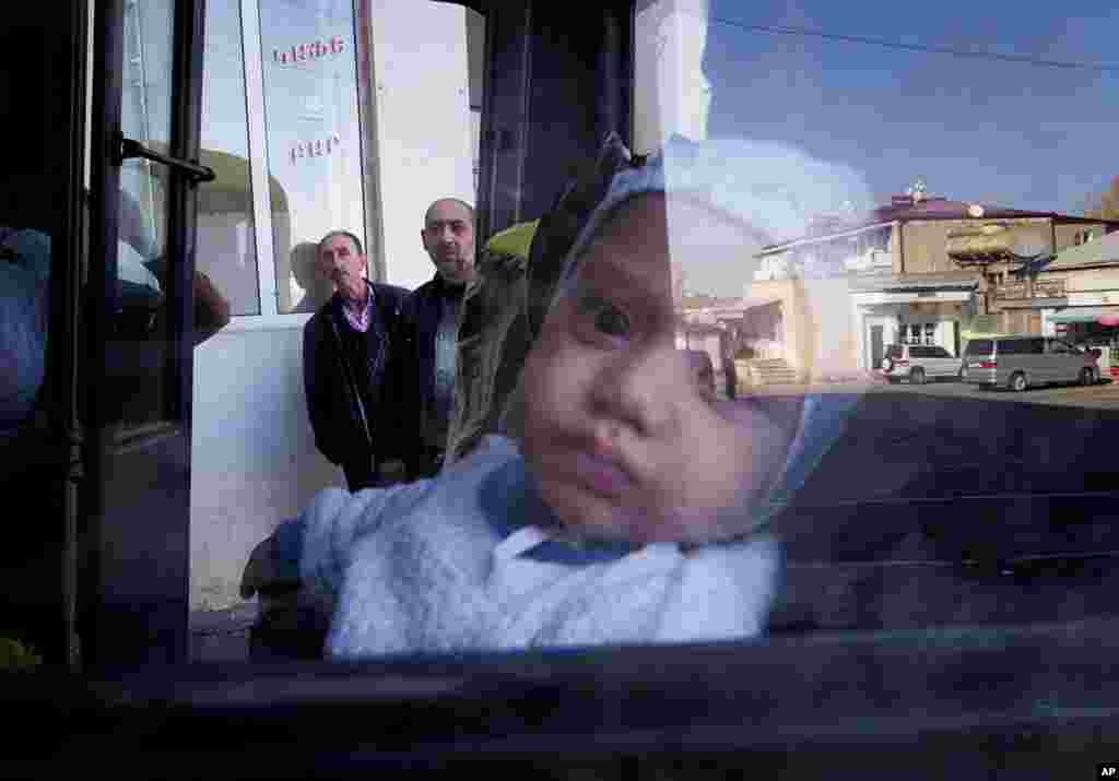 A street is reflected in a window as a baby and his mother prepare to leave Stepanakert amid fighting between Armenian and Azerbaijani forces around the breakaway region of Nagorno-Karabakh. (AP)
