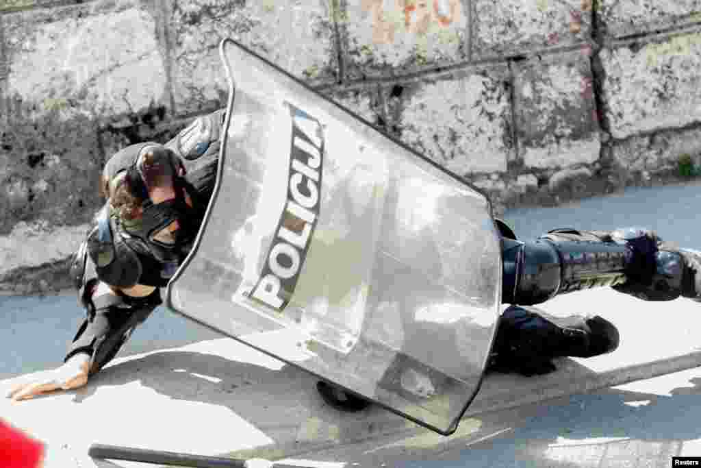 Полицаец паѓа на протестот против устоличувањето во Цетиње на црногорско-приморскиот митрополит Јоаникие на Српската православна црква.