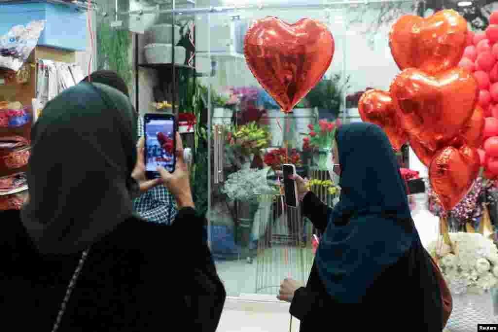Жінка фотографує подругу, яка тримає повітряну кульку у формі серця напередодні Дня святого Валентина в Ер-Ріяді, Саудівська Аравія, 13 лютого 2021 року