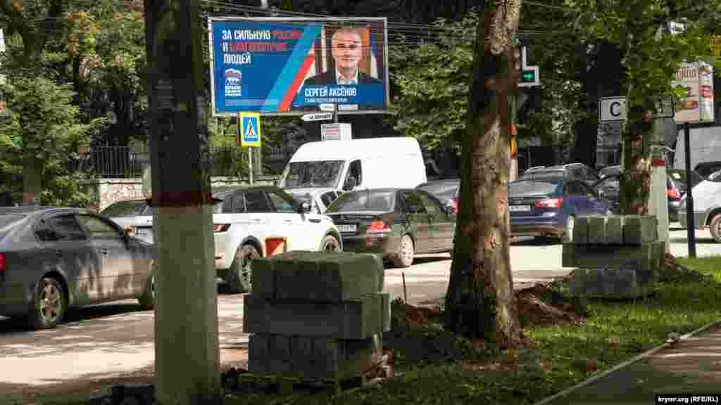 А с агитационного билборда «смотрит» на дорожников российский глава Крыма Сергей Аксенов