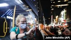 Медицинский работник, возвращающийся со смены, приветствует через стекло автобуса одного из протестующих в центре Нью-Йорка, 4 июня 2020 года