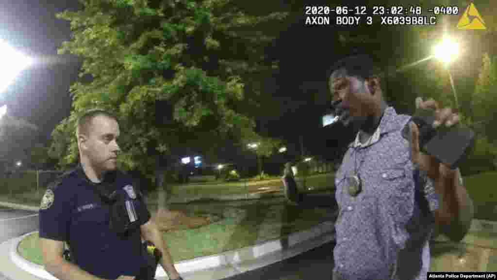 This screen grab taken from body camera video provided by the Atlanta Police Department shows Rayshard Brooks speaking with Officer Garrett Rolfe in the parking lot of a Wendy's restaurant, late Friday, June 12, 2020, in Atlanta. Rayshard Brooks was later shot in the back by the Officer Garrett Rolfe. Rolfe has been fired following the fatal shooting of Brooks and a second officer has been placed on administrative duty. The Georgia Bureau of Investigation (GBI) is probing the shooting death of Rayshard Brooks, 27, after a reported struggle with officers ensued during which a Taser was used late 12 June 2020.