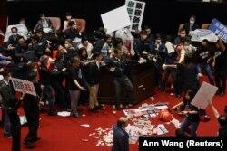 A fizikai erejük erejük mellett disznóbelet is bevetettek a tajvani Kuomintang képviselői a helyi parlamentben, 2020. november 27-én.