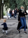 A woman wearing a protective mask plays with a child near Pincio Terrace, in Rome, Italy October 13, 2020.