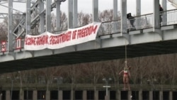 Femen Activist Hangs From Paris Bridge In Anti-Rohani Protest