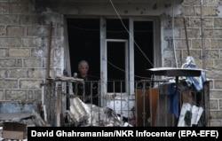 Egy nő egy sérült sztepanakerti épület ablakában